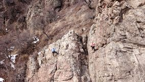 Climbers climb the rock. Drone footage. Side and top view. Rock lesson in the highlands. Gray rocks and dry bushes. Sometimes ther. E is snow. Steep rock and royalty free stock images