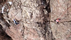 Climbers climb the rock. Drone footage. Side and top view. Rock lesson in the highlands. Gray rocks and dry bushes. Sometimes ther. E is snow. Steep rock and stock photo