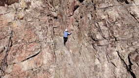 Climbers climb the rock. Drone footage. Side and top view. Rock lesson in the highlands. Gray rocks and dry bushes. Sometimes ther. E is snow. Steep rock and stock images