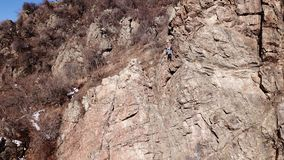 Climbers climb the rock. Drone footage. Side and top view. Rock lesson in the highlands. Gray rocks and dry bushes. Sometimes ther. E is snow. Steep rock and royalty free stock photo