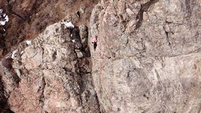 Climbers climb the rock. Drone footage. Side and top view. Rock lesson in the highlands. Gray rocks and dry bushes. Sometimes ther. E is snow. Steep rock and royalty free stock photos