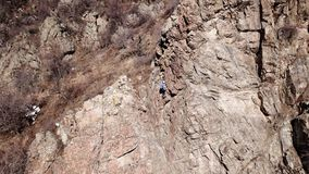 Climbers climb the rock. Drone footage. Side and top view. Rock lesson in the highlands. Gray rocks and dry bushes. Sometimes ther. E is snow. Steep rock and stock image