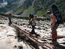 Climbers are crossing a mountain river. Caucasus, Russia. The climbers are crossing a flashy mountain river over the old wooden bridge in the gorge Adyr-Su Royalty Free Stock Photography
