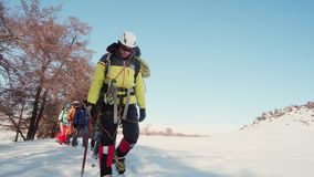 Climbers dressed in workwear follow each other on a footpath, Hiking sticks and pickaxes in hand.