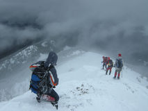 Climbers Enter Dark Snowy Abyss. Group of climbers going down to a steep snowy abyss. Winter storm in Slavyanka Mountain, Bulgaria Stock Photos