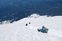 Climbers glissading down mountain summit. Climbers glissading down summit of Mt. St. Helens Royalty Free Stock Image