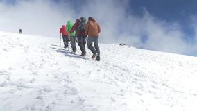 Climbers go up to the top on a snowy slope. On a nice sunny day. Mount Elbrus, Caucasus slow motion