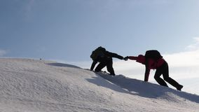 Climbers hand in hand climb to top of a snowy mountain. the team of travelers in winter go to their goal of overcoming. Climbers hand in hand climb to top of a stock image