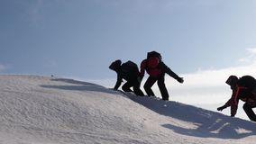 Climbers hand in hand climb to top of a snowy mountain. the team of travelers in winter go to their goal of overcoming. Climbers hand in hand climb to top of a royalty free stock photos