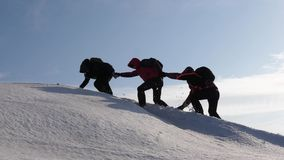Climbers hand in hand climb to top of a snowy mountain. the team of travelers in winter go to their goal of overcoming. Climbers hand in hand climb to top of a stock images