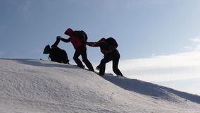 Climbers hand in hand climb to top of a snowy mountain. the team of travelers in winter go to their goal of overcoming. Climbers hand in hand climb to top of a stock photo