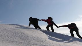 Climbers hand in hand climb to top of a snowy mountain. the team of travelers in winter go to their goal of overcoming. Climbers hand in hand climb to top of a royalty free stock photo