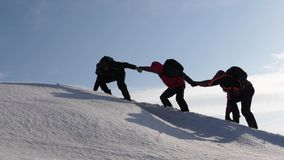 Climbers hand in hand climb to top of a snowy mountain. the team of travelers in winter go to their goal of overcoming. Climbers hand in hand climb to top of a royalty free stock photography