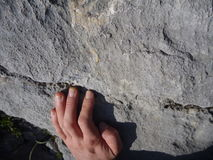 Climbers hand on a limestone cliff while climbing Stock Photo