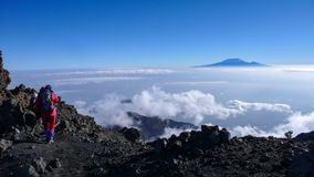 Climbers hike down from the summit of Mount Meru in Arusha National Park in Tanzania stock photography