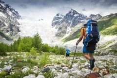 Climbers with hiking backpacks go to the mountain. hikers in mountains. Tourists hike on rocky mounts. Leisure activity on mountain trek in wild Svaneti region stock photography
