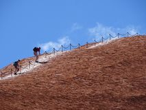Climbers ignore the no climbing sign. Uluru, Northern Territory, Australia 02/22/18. Climbers ignore the no climbing sign at the base of the rock royalty free stock photography
