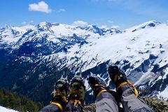 Climbers legs with boots and crampones against snow covered mountains. Stock Photos