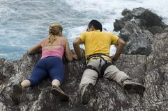 Climbers looking over cliff. Two middle aged climbers with equipment looking over top of cliff, sea in background Royalty Free Stock Photography