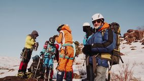 The climbers made a pass and are resting. one tourist passes the girl tea from a thermos bottle.  stock footage