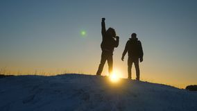 Climbers meet on top of snowy mountain and enjoy their success, raise their hands and jump joyfully. teamwork. Businessman. Men tourists with backpacks reached stock footage