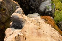 Climbers metal ladder via ferrata. Iron twisted rope fixed in block by screws snap hooks. The rope end anchored into sandstone roc Royalty Free Stock Photography
