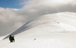 Climbers on the mountain. Two climbers with ice axe and crampons following a path on snow to a secondary summit Stock Photo