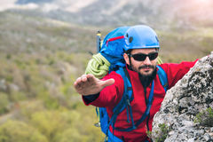 Climbers reaches the top of mountain peak, search help hand. Royalty Free Stock Photos