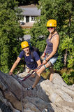 Climbers With Safety Equipment Relaxing On Rock Stock Photos