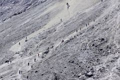 Climbers on the sandy track. Climbers pass the sandy climbing route of Mount Merapi, with an average slope of 70 degrees, Saturday, October 25, 2014. The line Stock Photos
