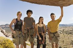 Climbers standing Underneath Rock Stock Photo