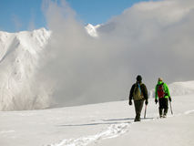 Climbers and summits. Two climbers with ice axe and crampons moving on snow, with summits and clouds in the background Stock Images