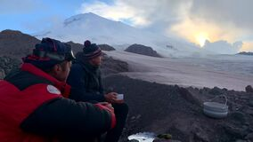 Climbers - travelers sit drinking tea with chocolates at the foot of Elbrus.