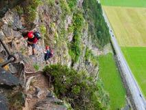 Climbers on via ferrata high above road Royalty Free Stock Photo
