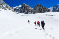 Climbers walk up on glacier Stock Photo
