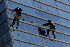Climbers washermen Windows. Athletes climbers wash Windows in high-rise buildings Royalty Free Stock Photography