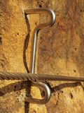 Climbers way. Iron twisted rope fixed in block by screws snap hooks.  The rope end anchored into sandstone rock. Royalty Free Stock Image