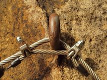 Climbers way. Iron twisted rope fixed in block by screws snap hooks.  The rope end anchored into sandstone rock. Royalty Free Stock Images
