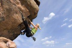 Climbig della giovane donna una roccia Fotografia Stock Libera da Diritti