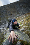 Climbing. Man trying to find his direction with a compass during climbing Stock Photos