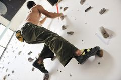 Climbing. Young and fit man exercise free mountain climbing on indoor practice wall Royalty Free Stock Photos