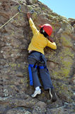 Climbing. Boy climbing rocks, wearing a harness and a hard hat royalty free stock photos