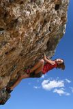 Climbing. Young woman climbing and stretching  nearly at the summit, on a rock face Royalty Free Stock Images