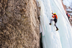 Climbing. Man climbing frozen waterfall in sunny day Stock Image
