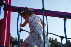 Climbing activities on the children playground. A little girl on a playground. Climbing activities on the children playground. A little girl playing on a royalty free stock images