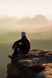 Climbing adult man at the top of  rock with beautiful  aerial view of the deep misty valley bellow Stock Photo