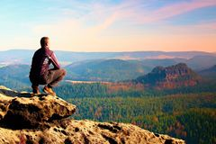 Climbing adult man at the top of  rock with beautiful  aerial view of the deep misty valley bellow Stock Photos