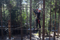Climbing in adventure park. Woman climbing on a rope in an adventure park in a forest stock photos