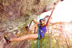 Climbing alpinist practicing outdoors at sunny day. Bottom view portrait of female climbing alpinist practicing outdoors at sunny day Stock Photos