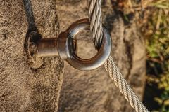 Climbing anchor or carabiner attached to rock. Climbing anchor or carabiner attached to the cliff rock. Difficult path for climbing on via ferrata royalty free stock photos